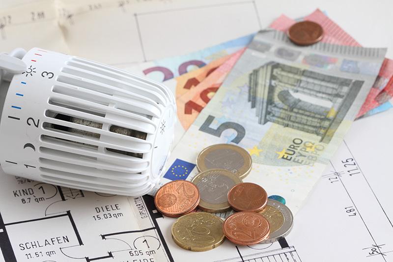 Heizungsthermostat mit Geldscheinen auf einem Bauplan